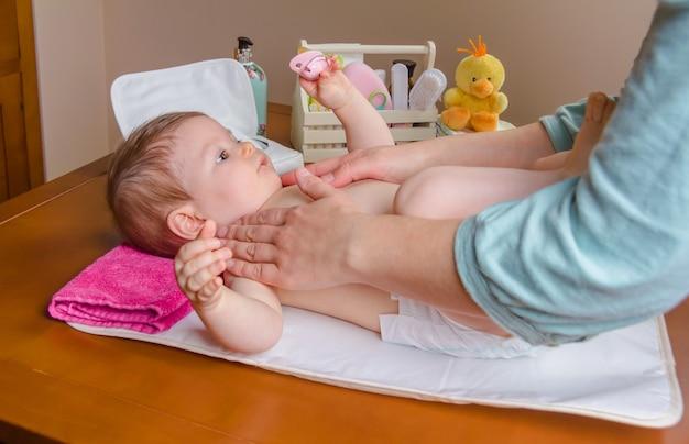 Moeder masseert het lichaam van een schattige baby die ligt na het verschonen van de luier