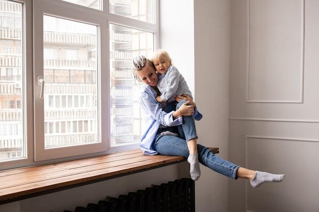 Moeder met baby bij het raam zitten en spelen
