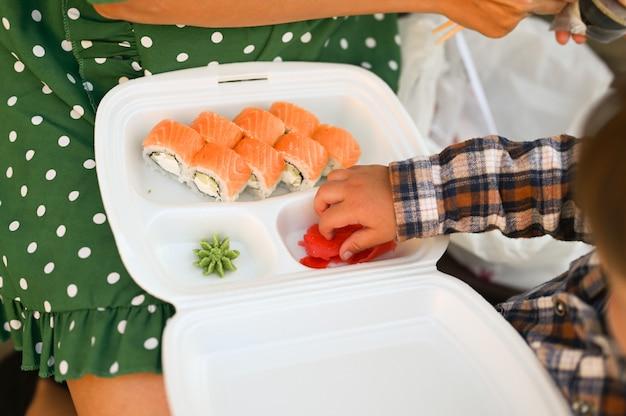Moeder met baby eten sushi op straat op straat