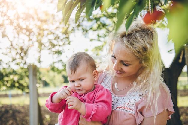 Moeder met baby het plukken kers in tuin