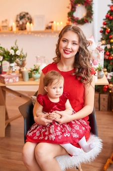 Moeder met baby in de keuken ingericht voor kerstmis.
