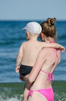 Moeder met baby in zwempak die het overzees bekijken