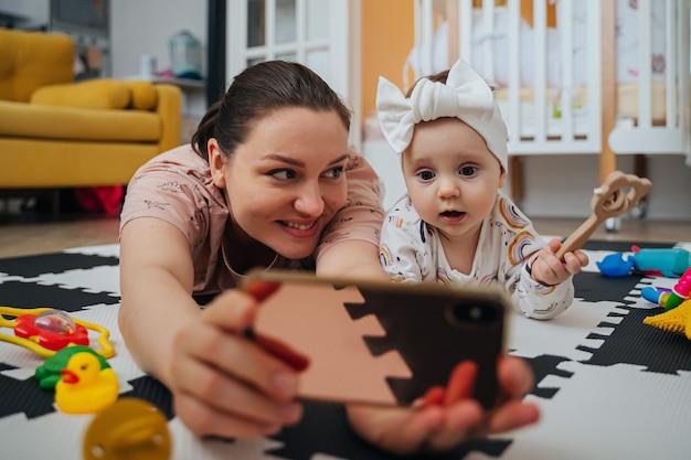 Moeder met baby kijken naar tekenfilm op smartphone