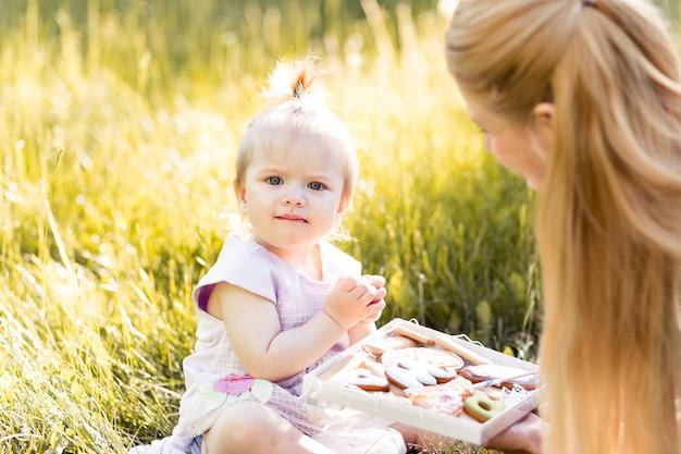 Moeder met baby, lachen en spelen in de zomerdag op de natuur