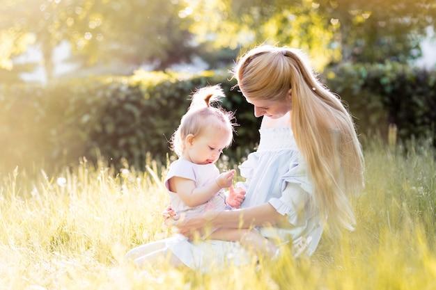 Moeder met baby, lachen en spelen in de zomerdag