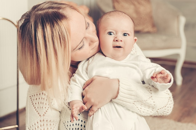 Moeder met baby zit bij de open haard in een gezellige woonkamer. foto met kopieerruimte