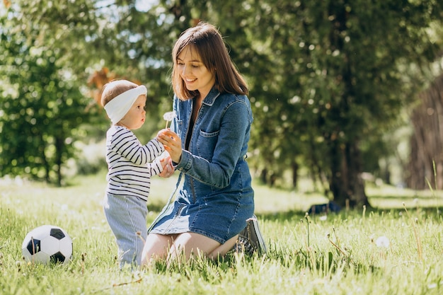 Moeder met babymeisje die met bal in park spelen