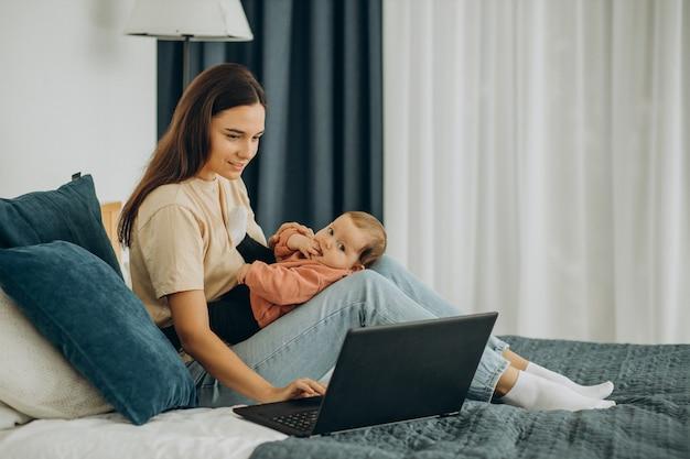 Moeder met babymeisje die thuis op de computer werkt