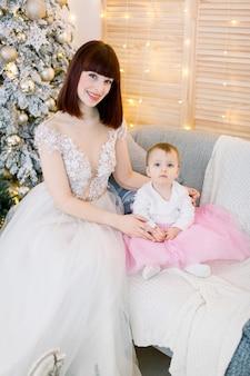 Moeder met babymeisje, jurken dragen, zittend op de bank op de achtergrond van de kerstboom
