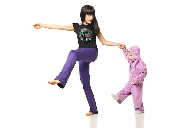 Moeder met de baby die oefeningen over wit doet