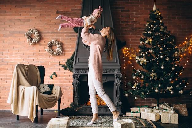 Moeder met dochter bij de open haard op kerstmis