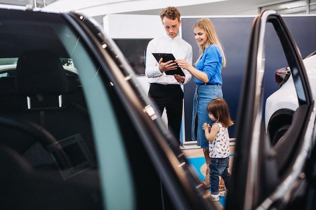 Moeder met dochter die aan verkoper in een autotoonzaal spreekt