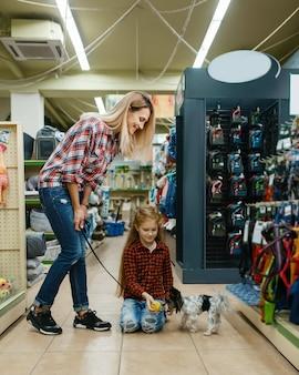 Moeder met dochter die bal kiest voor hondje in dierenwinkel. vrouw en klein kind kopen uitrusting in dierenwinkel, accessoires voor huisdieren