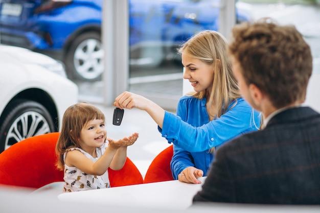 Moeder met dochter die een auto in een autotoonzaal koopt