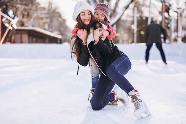 Moeder met dochter die het schaatsen op een piste onderwijzen