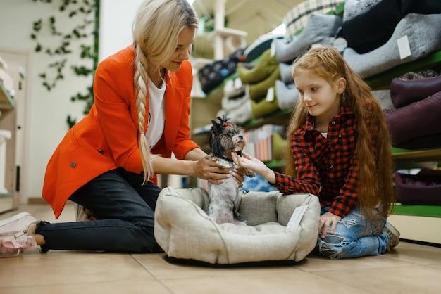 Moeder met dochter die hondenbed kiest voor kleine hond in dierenwinkel. vrouw en klein kind kopen uitrusting in dierenwinkel, accessoires voor huisdieren