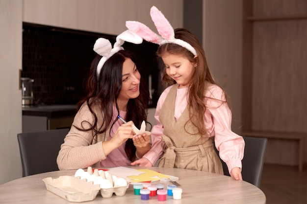 Moeder met dochter die konijnenoren dragen die thuis paaseieren verfraaien