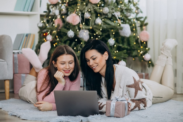 Moeder met dochter die online op kerstmis winkelt