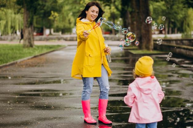 Moeder met dochter die pret in park in een regenachtig weer hebben