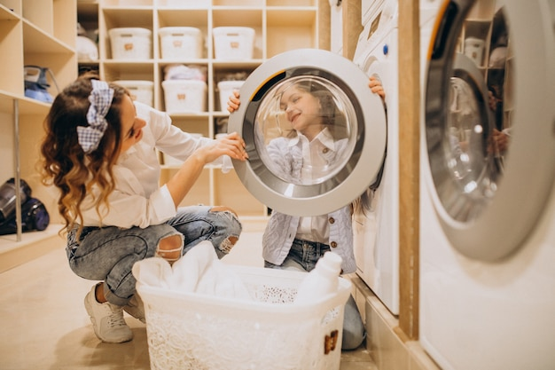 Moeder met dochter die wasserij doet bij zelfbedieningswasserette