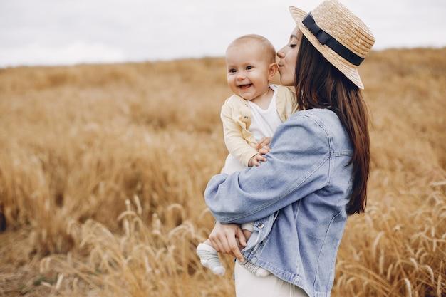 Moeder met dochter het spelen op een de herfstgebied