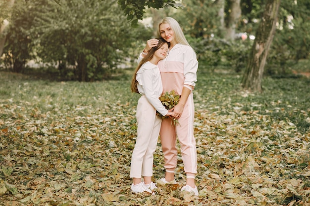 Moeder met dochter het stellen in een de zomerpark