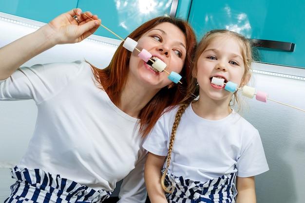 Moeder met dochter in de turquoise keuken eet marshmallows. mooie familierelaties. gelukkig familieconcept, gelukkige ouders en kinderen