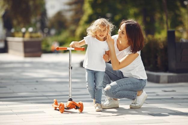 Moeder met dochter in een de lentepark met skate
