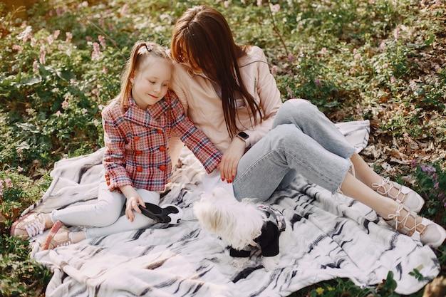 Moeder met dochter in een voorjaar bos met hond