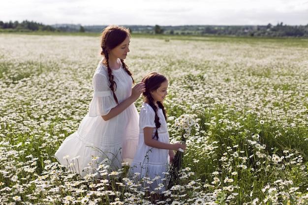 Moeder met dochter in een witte jurk en hoed staan in een madeliefjegebied in de zomer