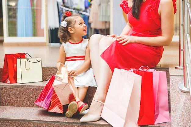 Moeder met dochter in jurken zitten op de trap in het winkelcentrum met gekleurde tassen