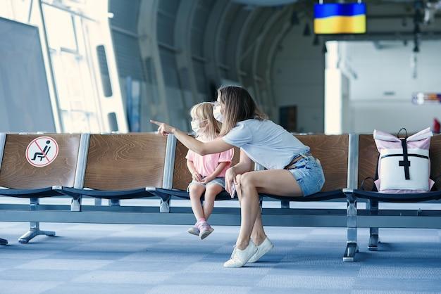Moeder met dochter in maskers die op hun vlucht wachten bij luchthavenvrouw met klein meisje in