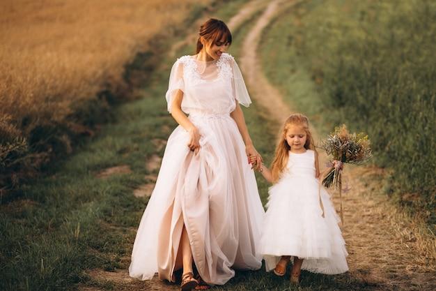 Moeder met dochter in prachtige jurken in veld
