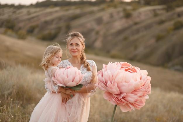 Moeder met dochter in roze sprookjesachtige jurken lopen in de natuur. de kindertijd van de kleine prinses. grote roze decoratieve bloemen