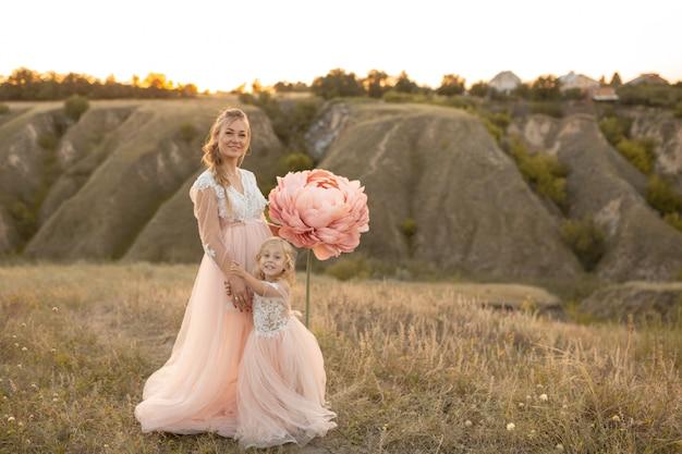 Moeder met dochter in roze sprookjesachtige jurken lopen in de natuur. de kindertijd van de kleine prinses.