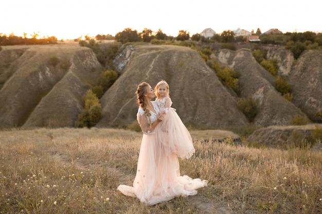 Moeder met dochter in roze sprookjesachtige jurken lopen in de natuur. kleine prinses jeugd