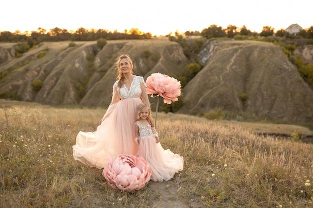 Moeder met dochter in roze sprookjesachtige jurken lopen in de natuur