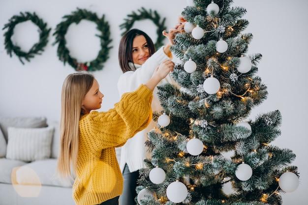 Moeder met dochter kerstboom versieren