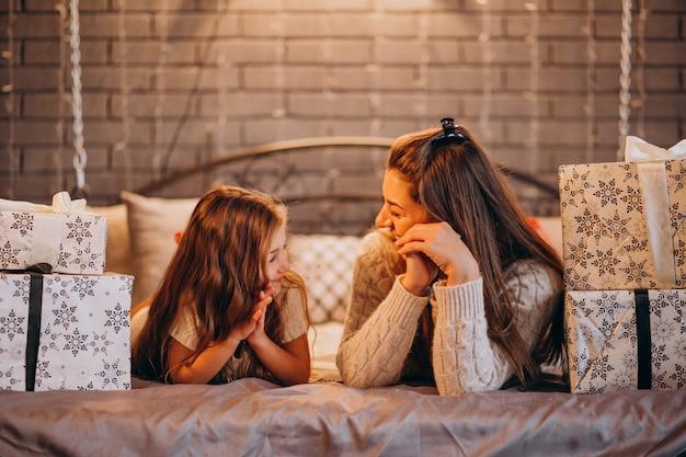 Moeder met dochter liggend in bed op kerstmis