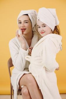 Moeder met dochter. meisjes met witte badjassen. moeder leert dochter make-up te doen.