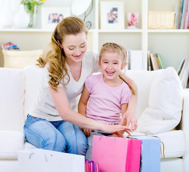 Moeder met dochter met boodschappentassen thuis