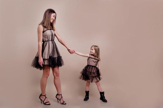 Moeder met dochter op geïsoleerde muur gekleed in soortgelijke jurken en veel plezier samen