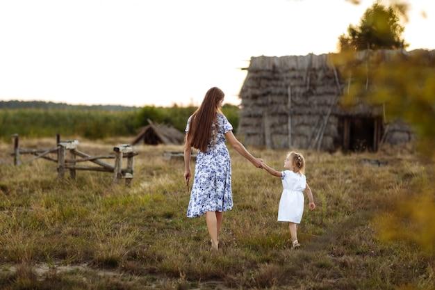 Moeder met dochter plezier samen buiten door het oude huis in het dorp