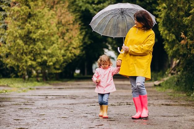 Moeder met dochter wandelen in de regen onder de paraplu