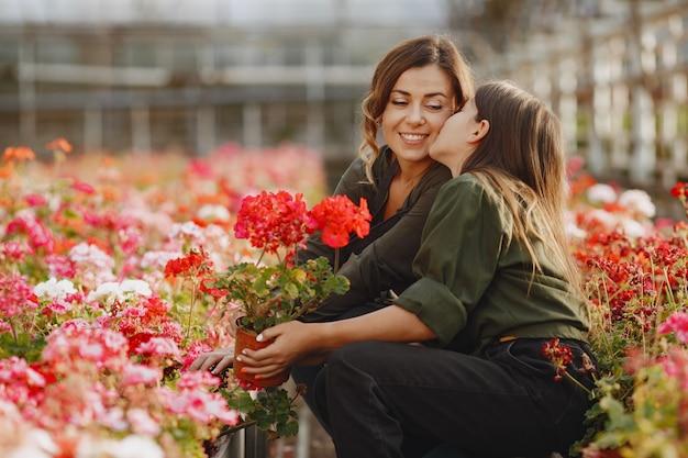 Moeder met dochter. werknemers met flowerpoots. meisje in een groen shirt