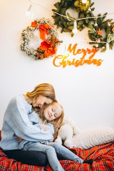 Moeder met dochter zittend op de sofa op kerstavond