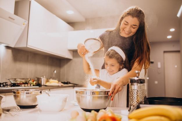 Moeder met dochterbaksel samen bij keuken