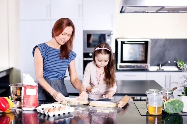 Moeder met dochtertje aan het koken