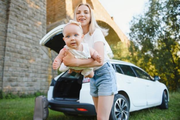 Moeder met dochtertje in de natuur in de buurt van de auto