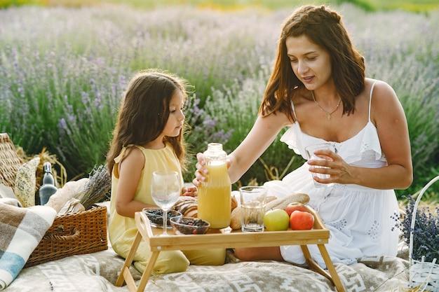 Moeder met dochtertje op lavendelveld. mooie vrouw en schattige baby spelen in weide veld. familie in een picknick.